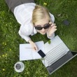 Young blonde woman working outside on computer — Stock Photo #5126137