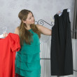 Woman chooses dress — Stock Photo