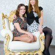 Two girls are sitting in a chair — Stock Photo
