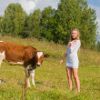 Girl and bull on a meadow — Stock Photo