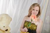 花とスイングにテディベアを持つ少女 — ストック写真