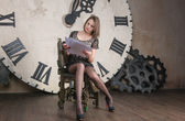 Beautiful girl working with documents in the background of the clock — Stok fotoğraf