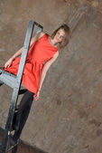 Beautiful girl on the steps of a stepladder — Stock Photo