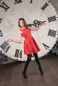 Young woman in red dress on a background of the clock — Stock Photo