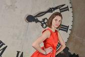 Giovane donna in abito rosso su uno sfondo dell'orologio — Foto Stock