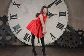 Ragazza bellissima in un abito rosso su uno sfondo di ore — Foto Stock