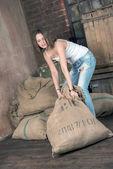 Beautiful girl drags heavy sack — Stock Photo