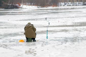 Fisherman fishing on the lake during the spring thaw — Stock Photo