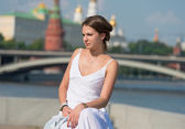 Beautiful girl in white dress sitting on the parapet of the embankment — Stock Photo