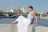 Happi girl in white dress sitting on the parapet — Stock Photo
