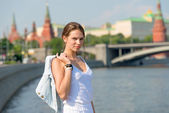Beautiful girl in white dress sitting on the parapet of the emba — Stock Photo