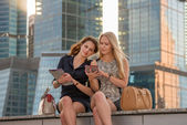 Two young woman resting near skyscrapers — Stock Photo