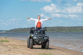 Young beautiful girl rejoices to freedom on ATV near the river — Stock Photo
