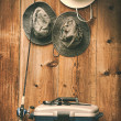 Stock Photo: Hats hanging on wall with fishing equipment