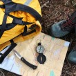 Hiking shoes on map with compass - Stock Photo