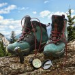 Pair of hiking boots with compass on fallen tree — Stock Photo
