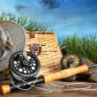 Fly fishing equipment with hat on wooden dock - Stock Photo