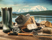 Fly fishing equipment on deck with view of a lake and mountains — Foto Stock