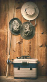 Hats hanging on wall with fishing equipment — Stock Photo