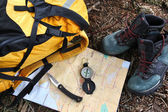 Hiking shoes on map with compass — Zdjęcie stockowe
