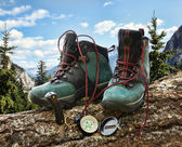 Pair of hiking boots with compass on fallen tree — Stock fotografie