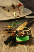 Fishing reel and hat on bench — Stock Photo