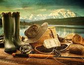 Equipamento de pesca com mosca no deck com vista para um lago e montanhas — Foto Stock