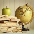 Old books with apple and globe - Stock Photo