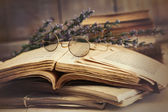 Old books open on wooden table — Stock Photo