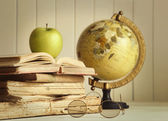 Old books with apple and globe — Stock Photo