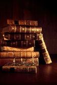 Zásobník starých knih s čtení brýle na stole — Stock fotografie
