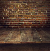 Old wooden table with brick background — Stock Photo