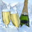Two glasses of champagne with bottle in snow - Stock Photo