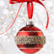 Stock Photo: Red Christmas ball with ribbon on sparkly background