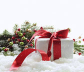 Gift box with red ribbon in snow on white — Stock Photo