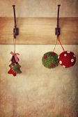 Holiday ornaments hanging on antique wall hooks — Stock Photo