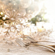 Elegantly lit holiday table with focus on pearl beads and utensi - Stok fotoğraf