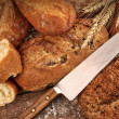 A selection of bread loaves with knife - Stock Photo