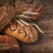 Assortment of loaves of bread on wood - Stock Photo