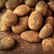Fresh potatoes on wooden background - Stock Photo