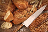 A selection of bread loaves with knife — Stock Photo