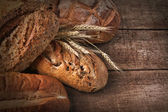 Assortment of loaves of bread on wood — Stock Photo