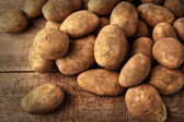 Fresh potatoes on wooden background — Stock Photo
