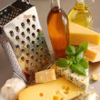 Stock Photo: Assortment of cheeses and olive oil on table