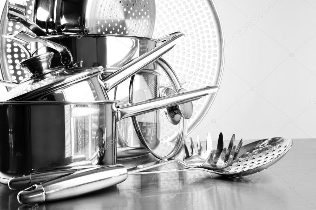 Stainless steel pots and untensils on table counter — Stock Photo #19277359