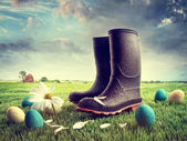 Rubber boots with easter eggs on grass — Stockfoto