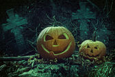Halloween pumpkins in graveyard at night — Stock Photo