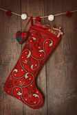 Christmas ornaments in stocking hanging on wood — Stock Photo