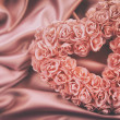 Heart made of pink roses on satin — Stock Photo