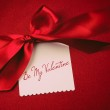 Red bow and white card for gift on velvet background — Stock Photo
